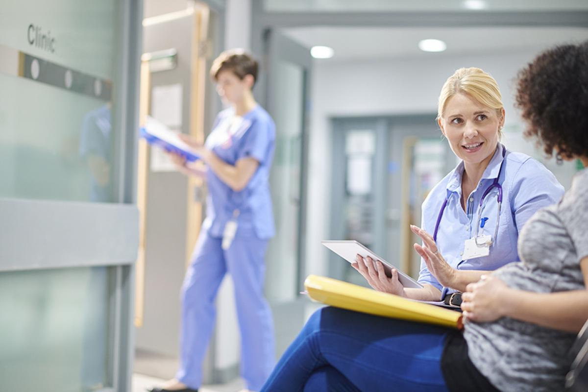 photo showing a nurse talking to a pregnant patient with another female nurse walking into a room