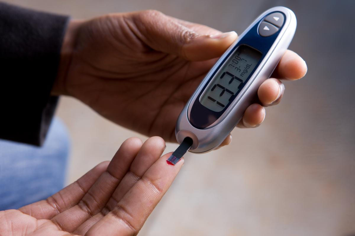 photo of a person checking their blood glucose level with a monitor