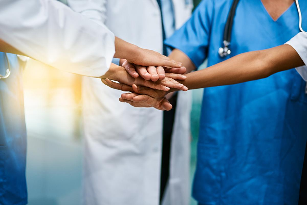 stock photo of medical professionals standing in a group with their hands overlapping each others in the center