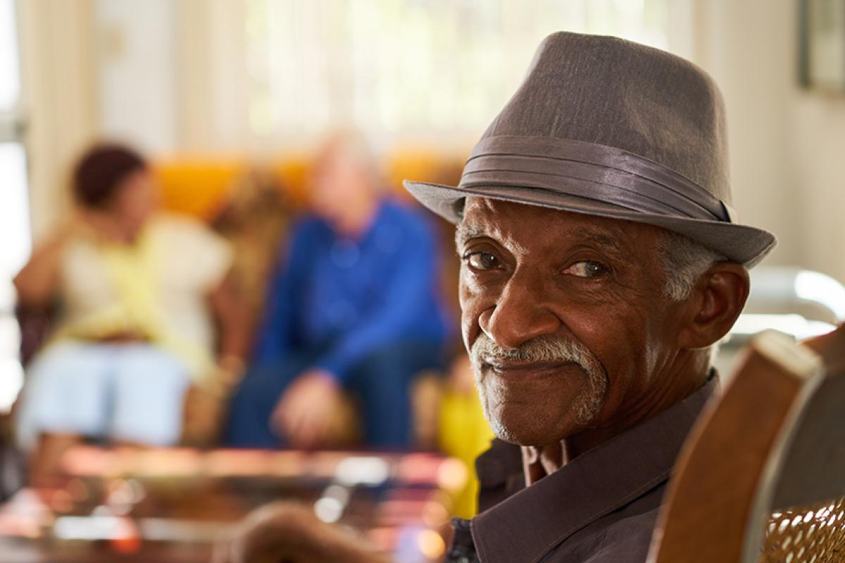 stock photo showing an older man in the forefront with two people sitting in the background