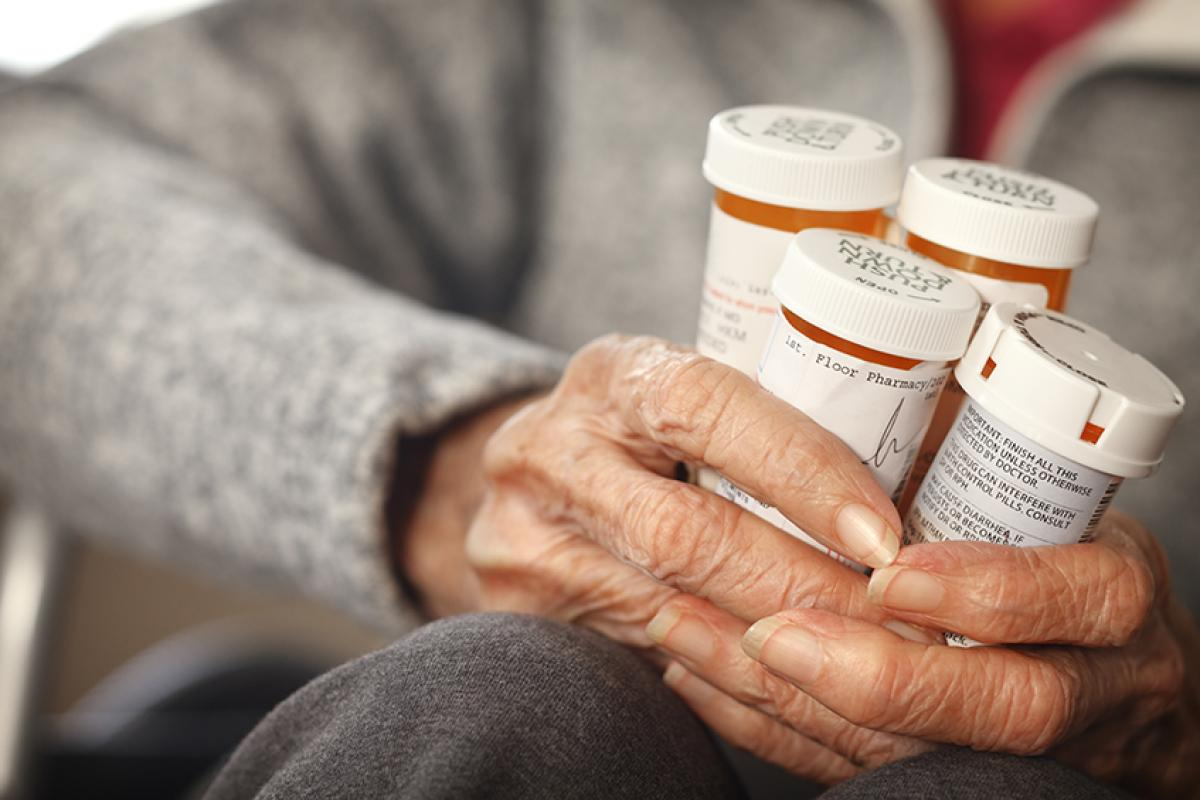 stock photo of an elderly patient's hand holding four bottles of medication