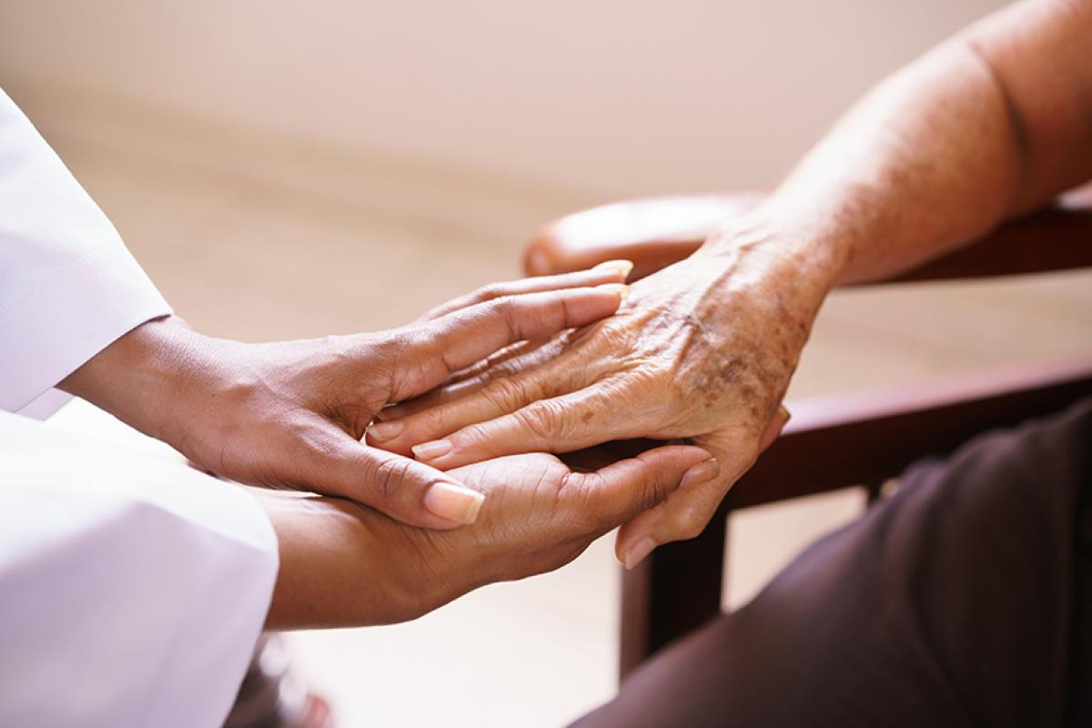 photo of a doctor holding the hand of an older patient